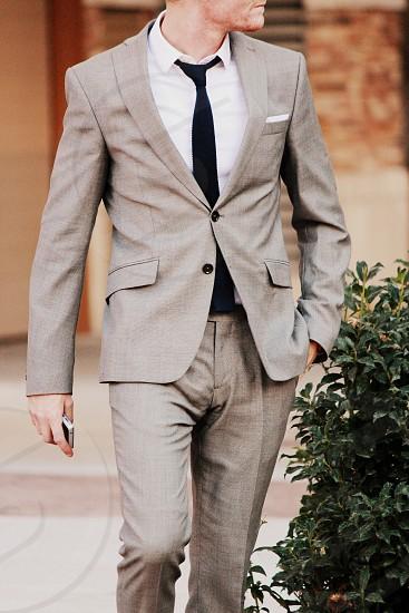 male model trendy fashion suit tie classy formal business man phone walking grey photo