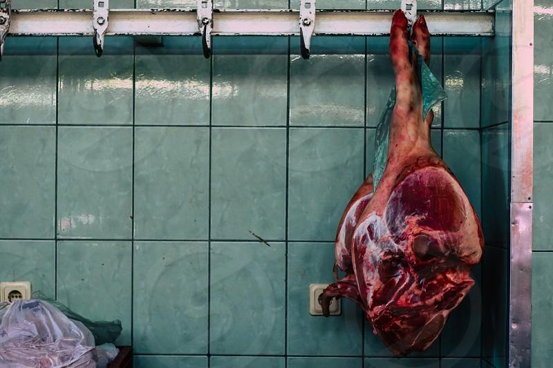 Fresh raw pork ham hanging at a market photo