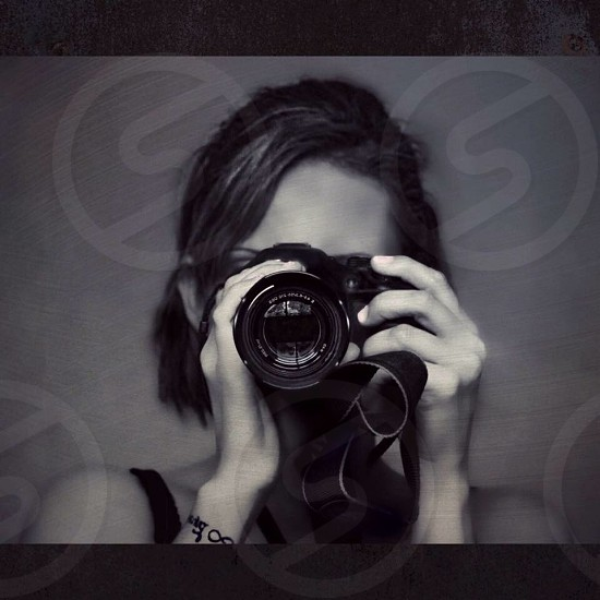 grayscale photography of woman holding DSLR camera photo