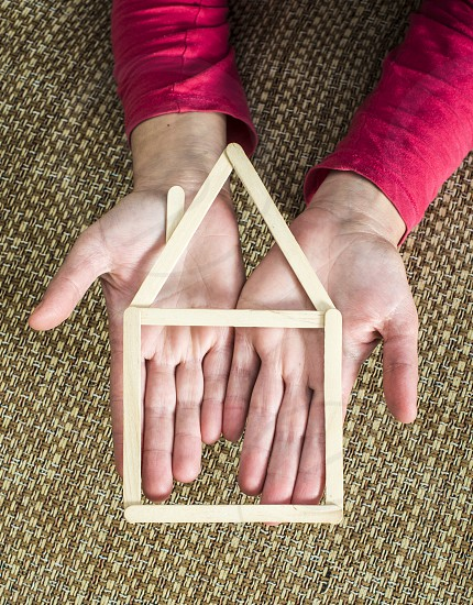 Hands holding model house made of wooden sticks placed in room interior. photo