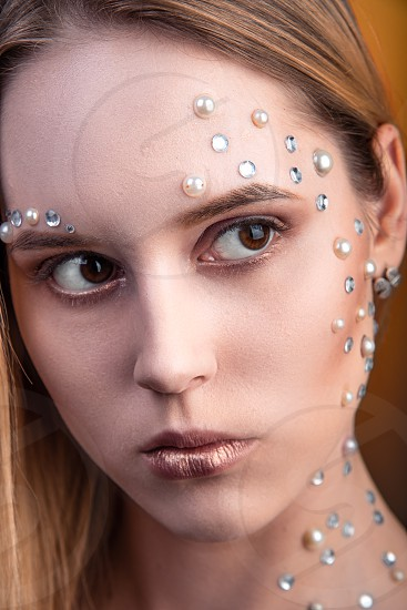 Portrait of a girl with original and creative makeup with white and pearl rhinestones photo