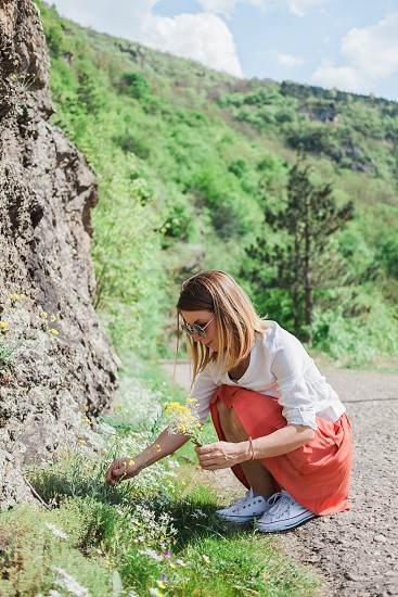Young woman picking flowers by the road photo