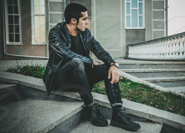 man wearing black leather jacket black jeans and black shoes sitting in stairway photo