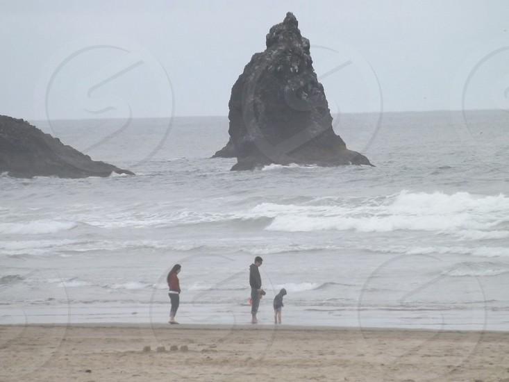 people wearing sweatshirts standing on beach photo