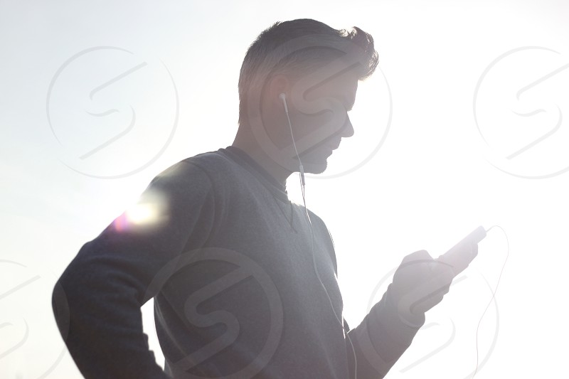 man wearing sweater looking at ipod photo