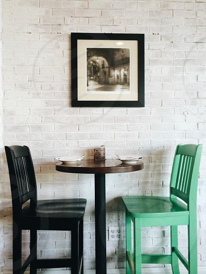 two mismatched chairs & small table at trendy restaurant with brick wall & artwork  photo