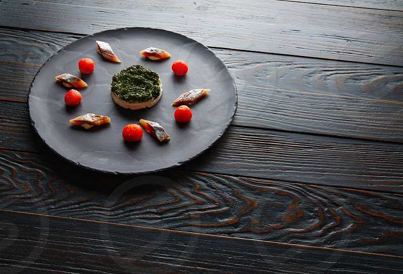 Bota sardine with white garlic pannacotta codium and osmotized tomatoes photo