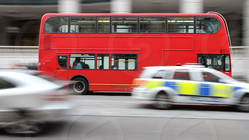 A blurred police car passing in front of an iconic red double deck bus on a busy road in London. photo
