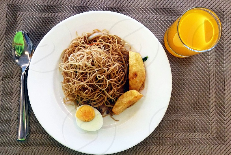 pasta sliced hard boil egg and fried potato on top beside orange juice on gray table mat photo