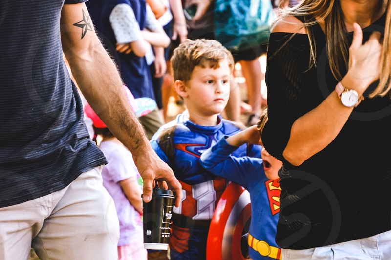 family outing parents children in superhero costumes Halloween festival  photo