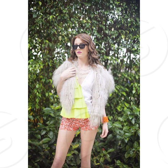 woman in white fur cape and yellow layered shirt with floral shorts wearing sunglasses photo