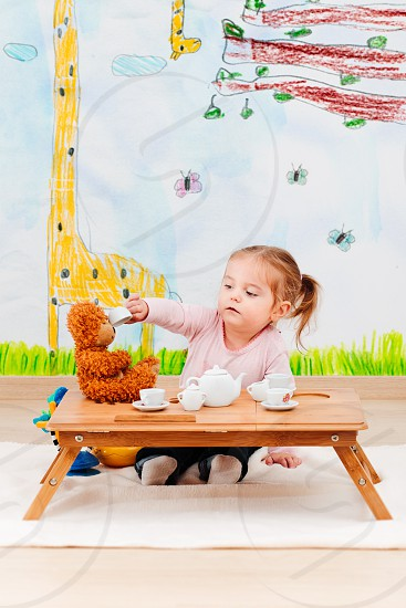 Little girl playing with her teddy bear at tea party using childs tea set photo