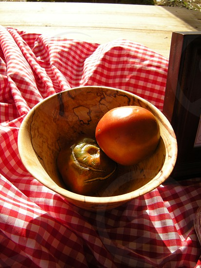Heirloom tomatoes in wooden bowl on checkered tablecloth photo