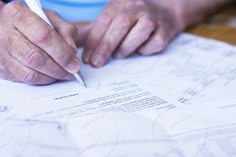 Older man signing papers for bank credit. photo