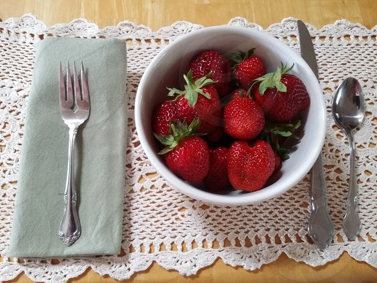 Breakfast at the dinner table  Strawberries bowl green cloth napkin fresh fork knife  spoon lace placemat landscape wood table photo