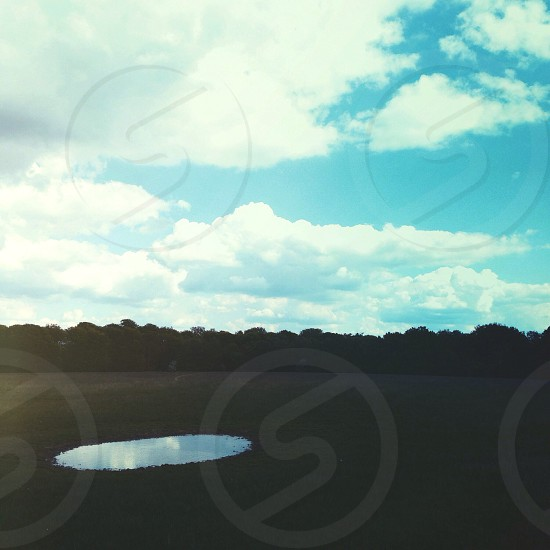 Empty puddle pond reflection visual echo sky field isolated desolate countryside cold blue green.  photo
