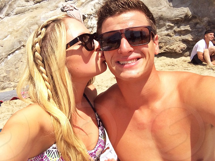 woman in purple and white swimsuit kissing man in black rimmed sunglasses photo