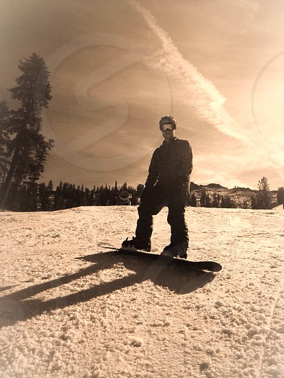 Snowboarding down the mountain in the cold snow  photo