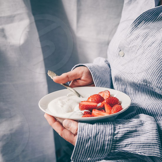 Woman's hands holding a bowl with strawberries photo