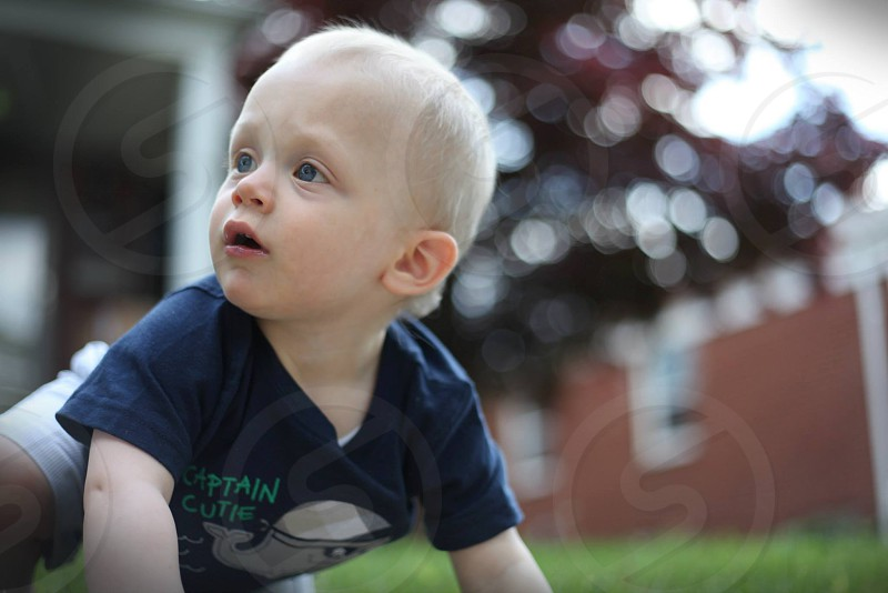 baby wearing blue short sleeve shirt with green lettering photo