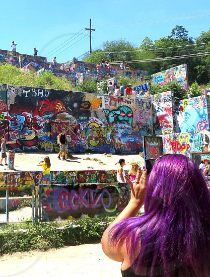 Woman with violet-purple hair taking photo Hope Outdoor Gallery Austin Texas photo