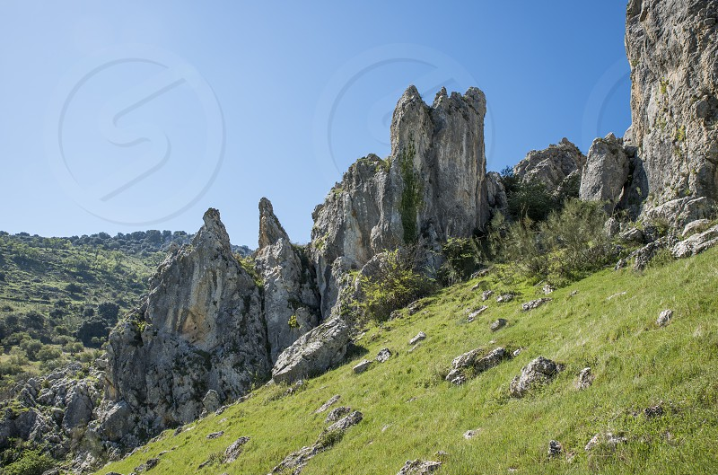 rocks and blue sky in andalusia with green grass landscape photo