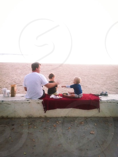 man sitting near the two toddlers with fringe red textile on their butt facing the body of water photo