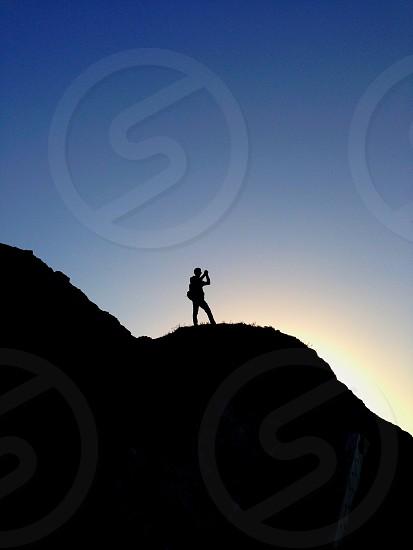man standing on rocks silhouette photo