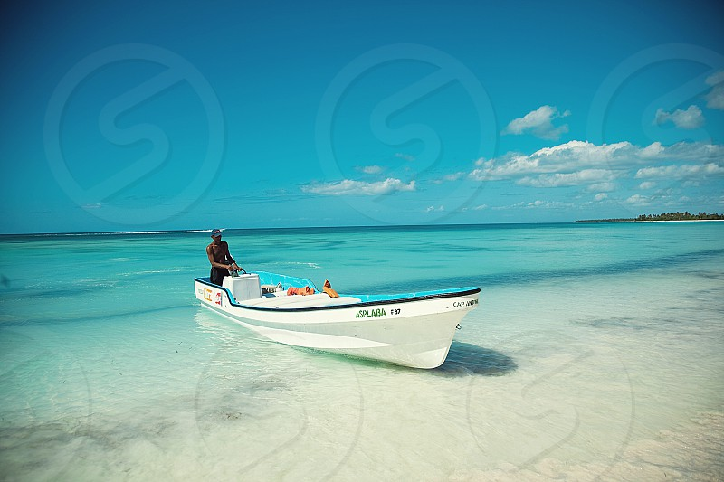 Caribbean nature captain in a boat in the turquoise sea photo