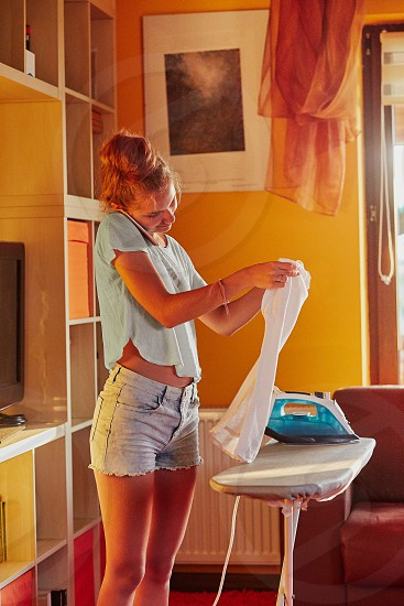 Young woman is ironing her clothes and talking on a smartphone simultaneously standing by a ironing board in a room at home. Routine housekeeping task at home. Candid people real moments authentic situations photo