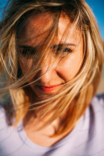 woman's face covered with her blonde hair in tilt shift lens photo