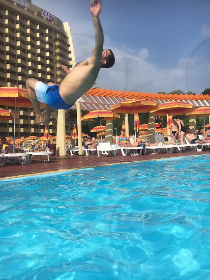 man back jumping over pool with orange and yellow cottages in background photo