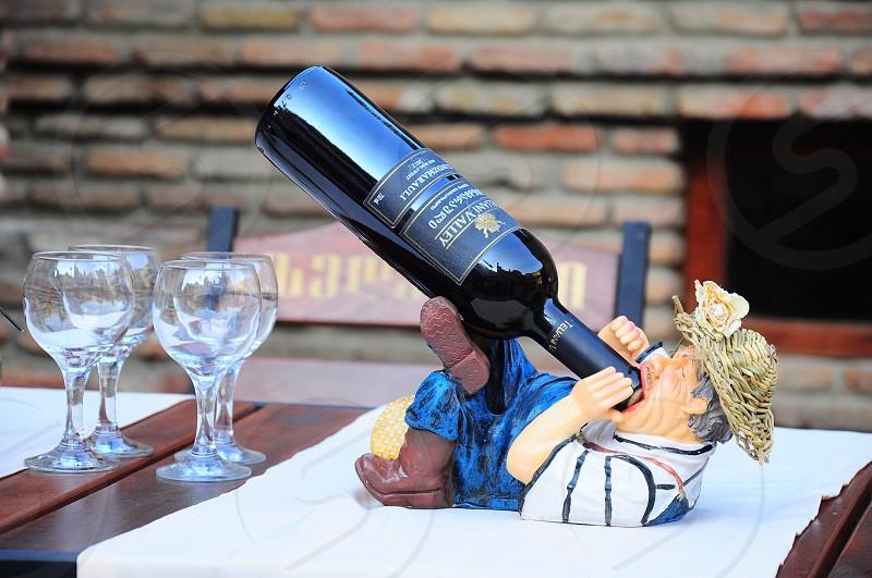 man in straw hat drinking from wine bottle holder near clear wine glasses photo