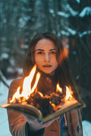 Female model holding a book burning in flames in the outdoors park location photo