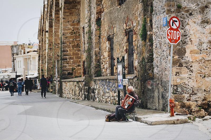 Street photography street musician street musician  man people sitting street sign photo