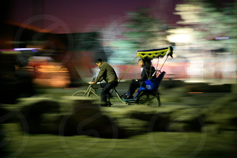 man in green bubble jacket driving tricycle with 2 passengers photo