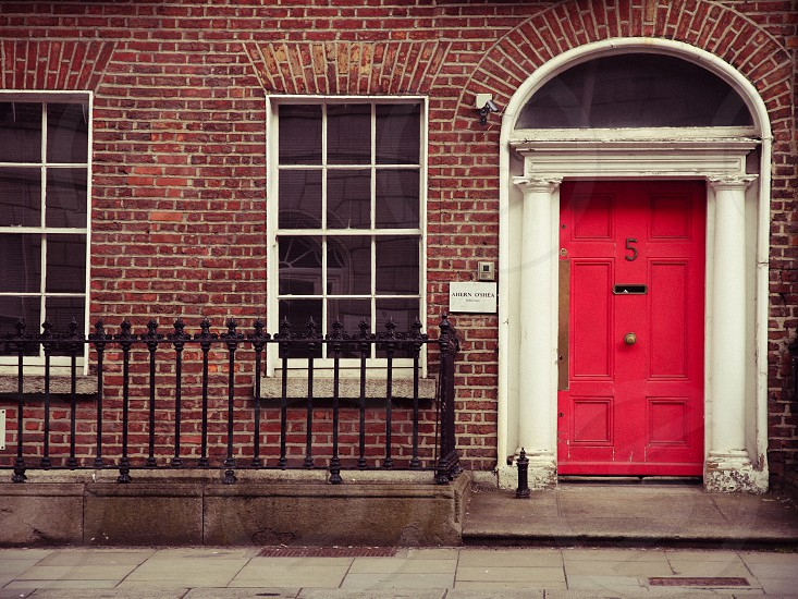 brown concrete house with red wooden door photo