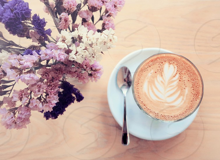 Cup of latte or cappuccino coffee and flowers photo
