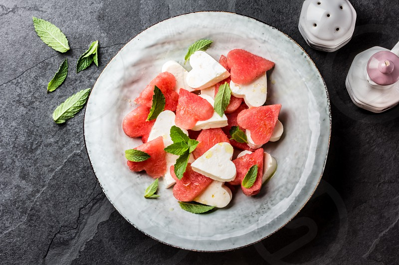 Mediterranean Italian Salad with watermelon and cheese feta cut as hearts and mint on grey plate on slate background. Valentine day menu consept. healthy food. Top view photo