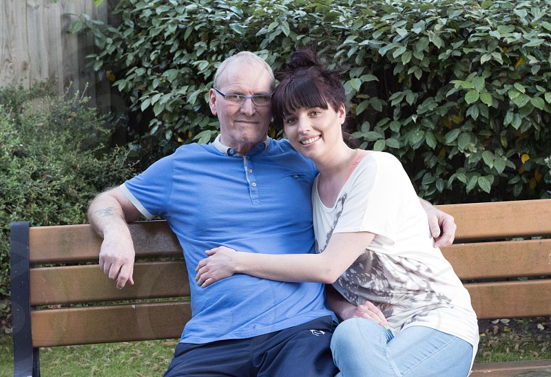 couple sitting on brown wooden outdoor bench photo