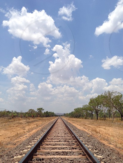 Railway tracks converging lines infinity parallel train bush outback trees lost forever clouds Sky blue journey photo