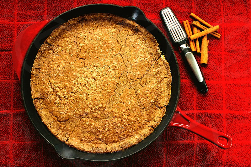 On the Table - Overhead view of a freshly baked Cinnamon Sourdough Dutch Baby in a red cast iron skillet with cinnamon sticks and mini-grater on a red towel photo