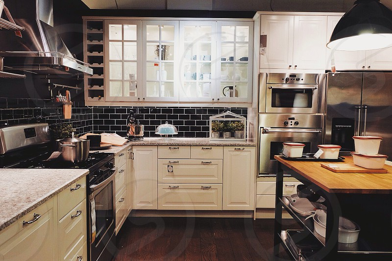 cottage white kitchen with black subway tile and wooden flooring photo