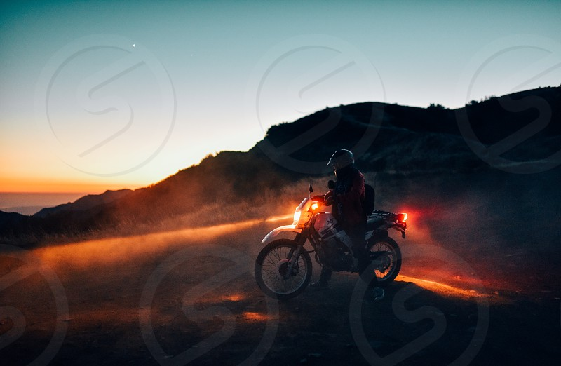motorbike motorcycle dirtbike dusk dawn dirt sunset dust dusty light headlight man mysterious adventure photo