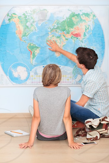 Teenagers sitting by the map in classroom photo