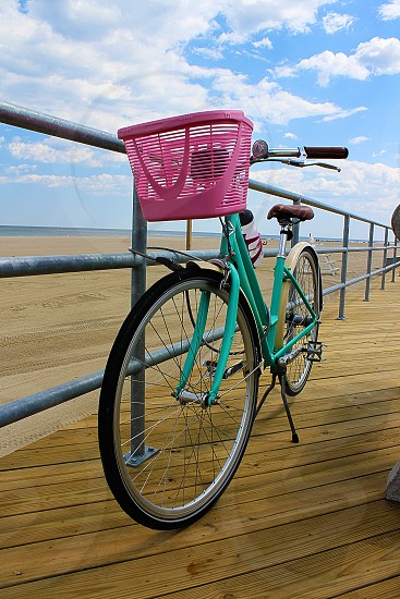 Ride the boardwalk on a teal bicycle at the shore. photo