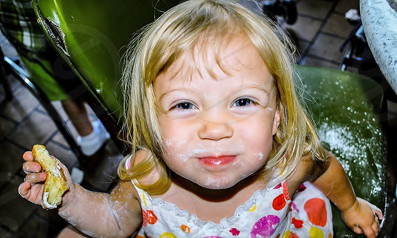 Little girl really enjoying beignets at New Orleans Cafe Du Monde in the French Quarter making a mess with the powdered sugar photo