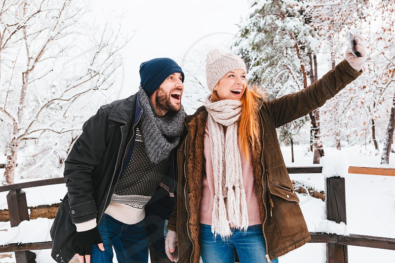 Young couple taking a selfie in a park on a snowy day photo