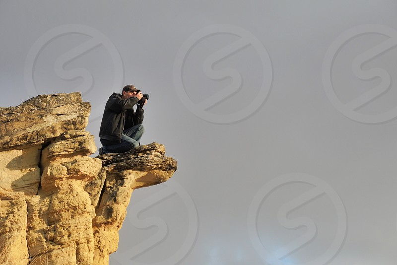 man in rock cliff taking a photo photo