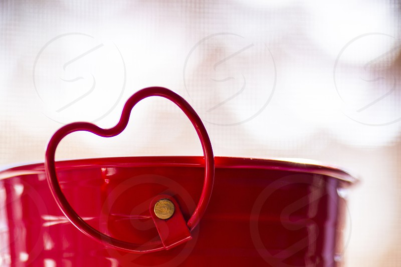 Red metal heart handle on a red flower can photo